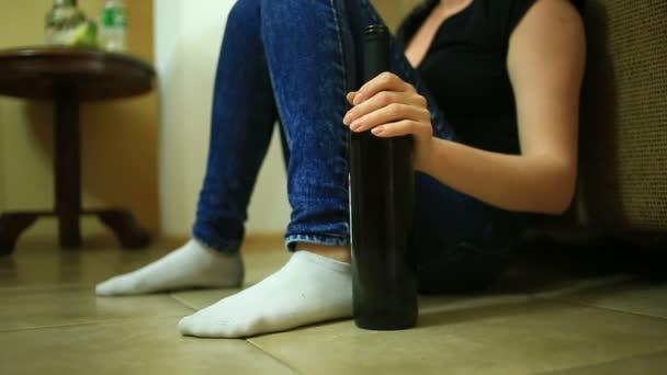 Alkoholfogyasztás, palackkal kezében nő nő. Üres üveg alkohol alatt a háttérben, egy asszony feküdt a padlón.