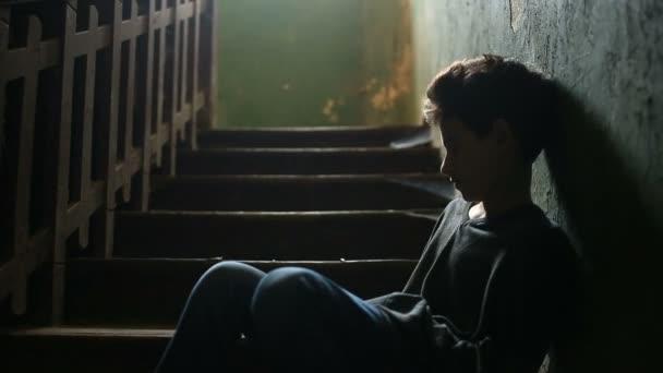 A fiú ül egy elhagyott veranda lépcsőin. A gyermek kábítószer-függőség, hódolnak, hajléktalanság fogalmát