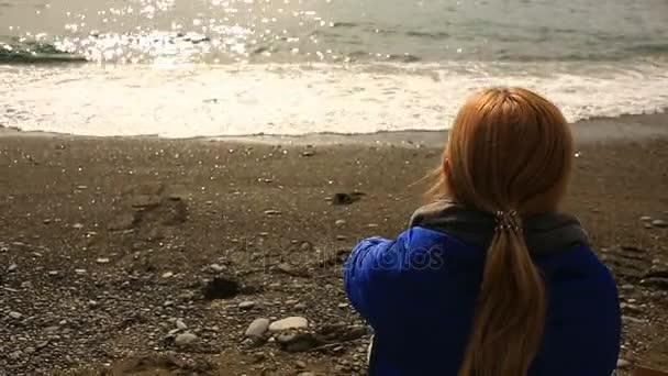 Žena sedí o samotě na opuštěné pláži za špatného počasí, se dívá na moře a žere pizzu