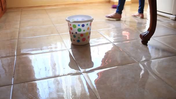 Žena myje podlahu v kuchyni s mopem. Namáčení hadr v barevné sady