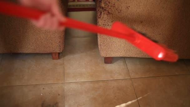Eine Frau fegt den Boden in der Küche, Esszimmer mit Pinsel und Schaufel. Close-up