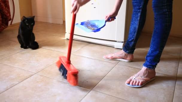 Žena vytírá podlahu v kuchyni, jídelna pomocí štětce a scoop. detail
