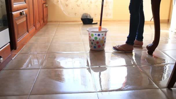 Žena myje podlahu v kuchyni s mopem. Namáčení hadr v barevné kbelík, pohled shora