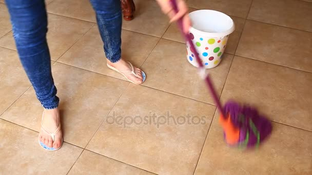 A woman washes the floor in the kitchen with a mop. Dipping a rag in a colorful bucket, view from above