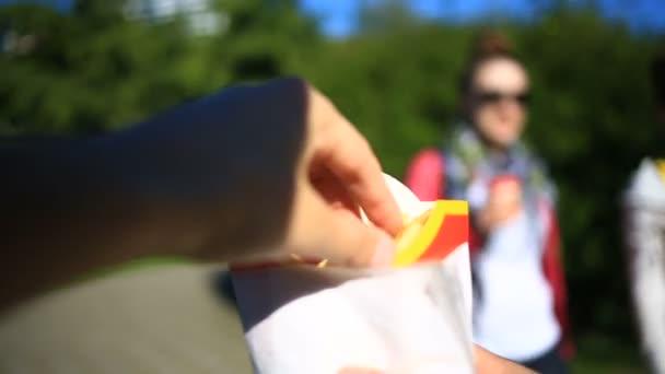 Muž jí rychlého občerstvení na ulici. Nese hranolky a jí to. Na pozadí rozmazané městské ulice