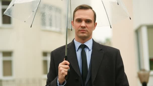 Frustrated by the weather, standing under the umbrella during the rain. Unhappy man in a suit