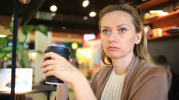 A woman is drinking coffee at a fast food cafe. Disposable cup. coffee to go