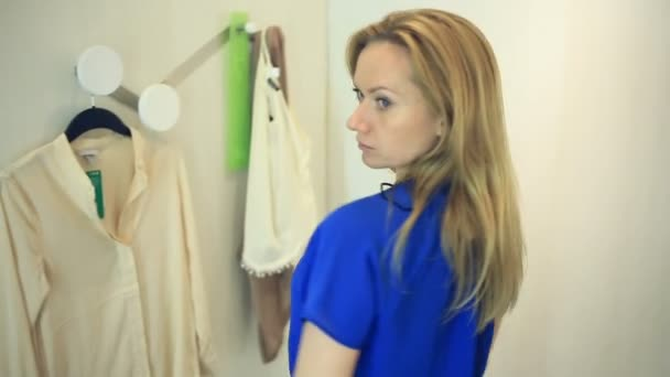 on sale ce706 f754d Acquisto della donna nel negozio di vestiti, scegliere i vestiti, una donna  cerca su abiti in uno spogliatoio, sguardi allo specchio