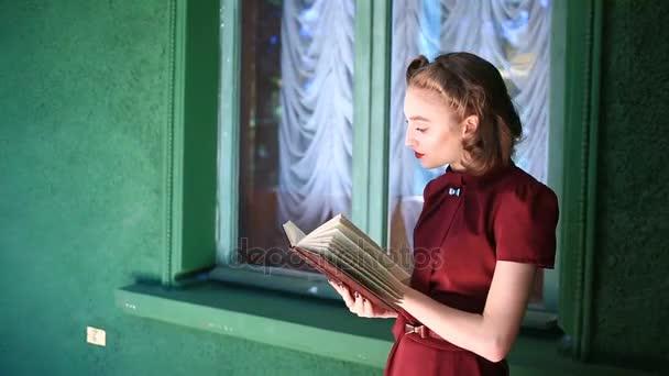 Šťastná dívka pin-up šaty retro styl. Dívka s pozitivní emoce. Model představuje pro fotografii střílet v retro stylu. Čte knihy na balkoně