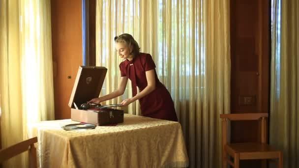 Šťastná dívka pin-up šaty retro styl. Dívka s pozitivní emoce. Představuje pro fotografa vedle retro hráč a vinyl disky