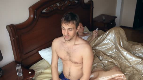 Man taking a pill before sex. A woman is waiting for a man in bed