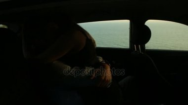 Young couple kisses in a car at night