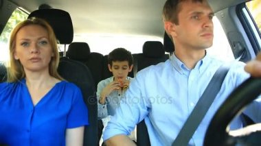 Family, mom dad and son riding in car, son eating hamburger
