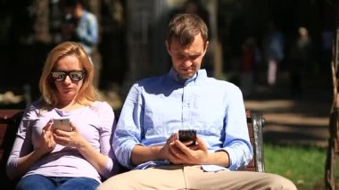 Man and woman looking in different directions, sitting on a bench. Everyone is looking at his mobile phone