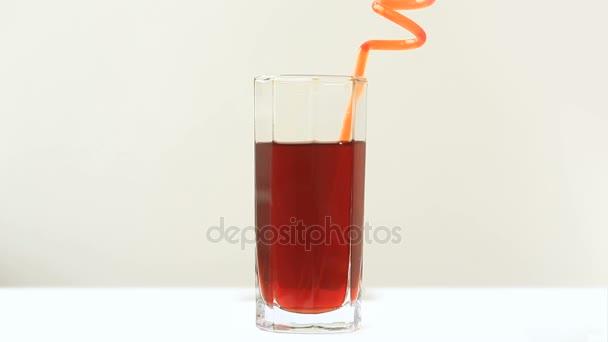 jemand trinkt den Saft durch ein Rohr zum Trinken. Nahaufnahme isoliert auf weißem Hintergrund.