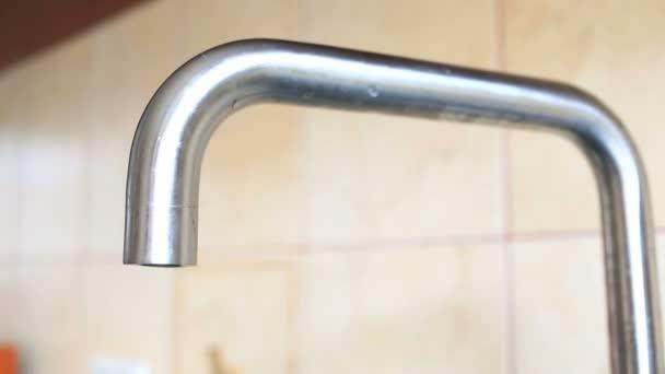 Primo piano di acqua che gocciola da un rubinetto da cucina