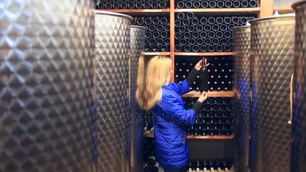 A woman chooses wine in a wine cellar.
