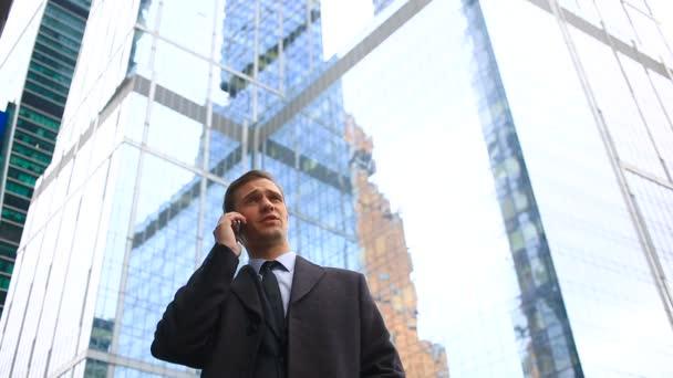 Üzletember a városban, a hívást a smartphone. A háttérben a felhőkarcoló