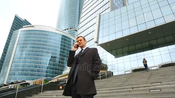 Obchodní muž v městě telefonní hovor s smartphone. Na pozadí mrakodrapů