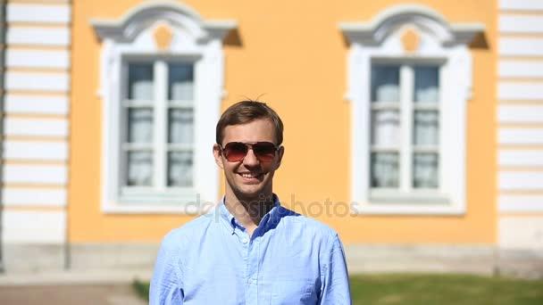 Pohledný mladý muž stojí v pozadí oken nádherný dům a usmívá se, při pohledu na fotoaparát
