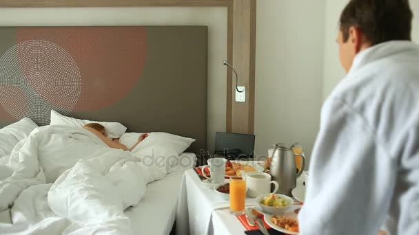Giovani coppie uomo e donna avendo la colazione sul letto in appartamento