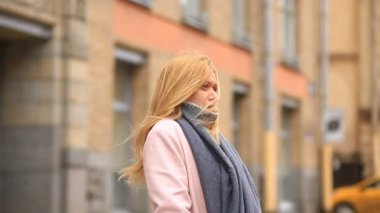 A tired woman in a pink coat and sweater stands in the middle of a crowded street and shrinks from the cold
