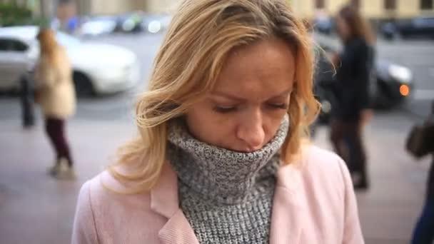 Unavená žena v růžové kabát a svetr stojí uprostřed přelidněné ulici a dívá do svého chytrého telefonu