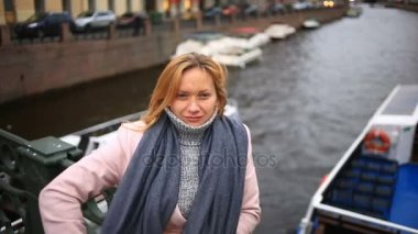 Woman in pink coat and sweater stands on bridge over water background and looks at camera