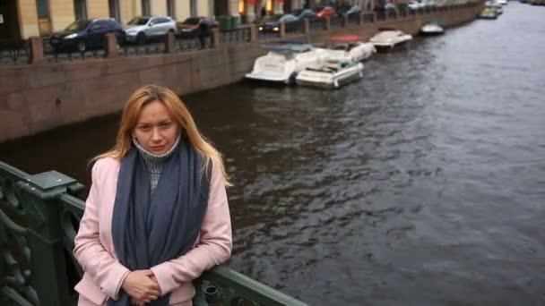 Žena v růžové kabát a svetr stojí na mostě přes vodní pozadí a dívá na kameru