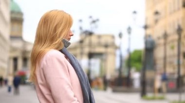 The camera slides around a woman who stands in the middle of a city street in a pink coat and scarf