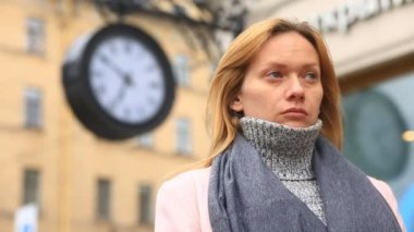 A woman in a pink coat and sweater is standing in the middle of a crowded street near the clock and waiting for the meeting