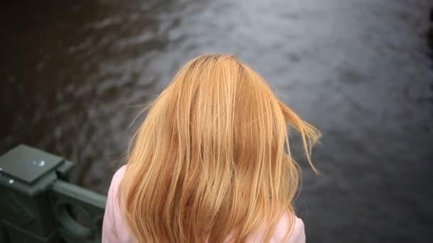 Eine Frau im Mantel steht auf einer Brücke und blickt auf das schwarze Wasser herab. Sie will Selbstmord begehen