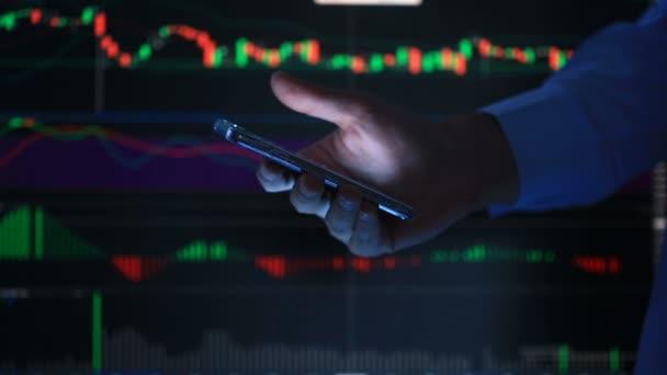 Kezét a személy a telefont, gépelés egy szöveges üzenetet a smartphone, a háttérben a Lcd képernyő-val a grafikon, a pénzügyi piaci csere - grafikon.