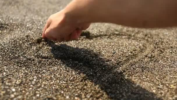 Ruka maluje srdce na hnědý písek