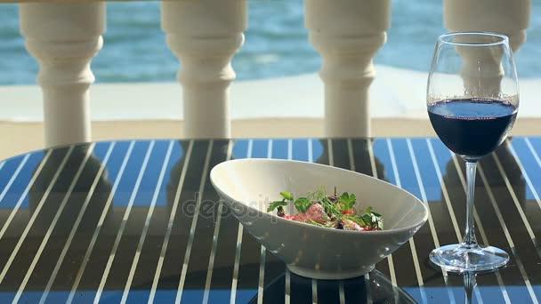 Eine Schüssel mit einem Gourmet-Restaurant. Close-up. Schweinefleisch mit Gemüse und ein Glas Rotwein. Restaurant am Meer