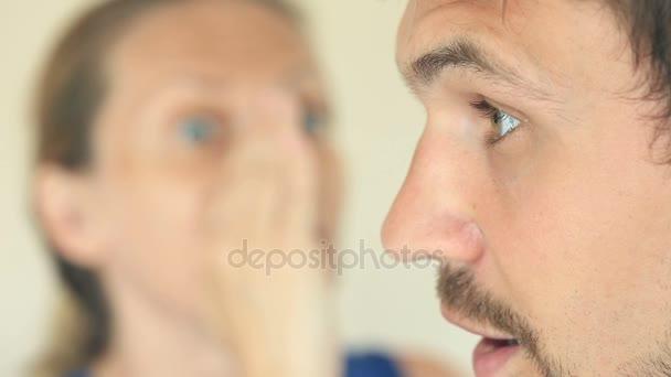 Žena, šeptá v mans ucha tajemství. HES překvapil a usmíval se. Profil muže zblízka. Zenske tvář je rozmazaný