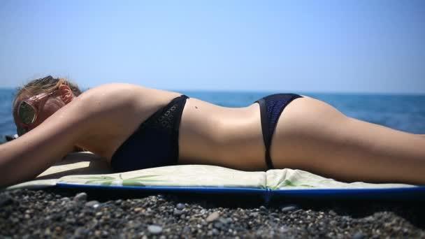 Nő, napozásra a strandon fekvő kövek