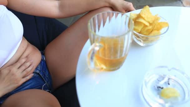 Tlustá žena pít pivo. Tlustá žena v krátké tričko a šortky je pití piva s čipy v pivním baru. Zpod vesty jsou vidět její záhyby tuku na břiše