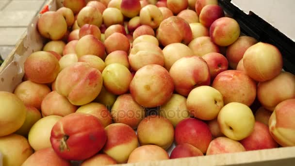 Egy nő a növényi polc, szupermarketben vásárol, zöldségek és gyümölcsök. Az ember úgy dönt, kajszibarack, őszibarack, nektarin. Lassú mozgás, 4k