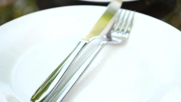 Prázdná bílá talíř a příbory na něm. vidlička a nůž. Zpomalený pohyb
