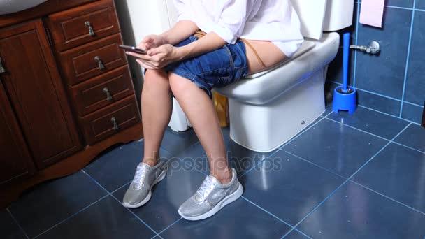 žena sedí na WC v koupelně. pomocí chytrého telefonu. 4k
