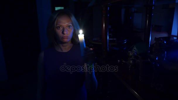 Egy nő sétál a sötétben a házban gyertyával a kezében. Halloween. Horror. 4 k. lassú mozgás