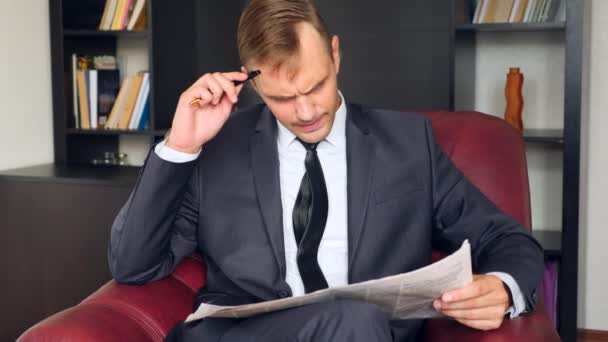The businessman is sitting in a chair and reading a newspaper. He is unhappy and expressive. 4 . Slow motion.