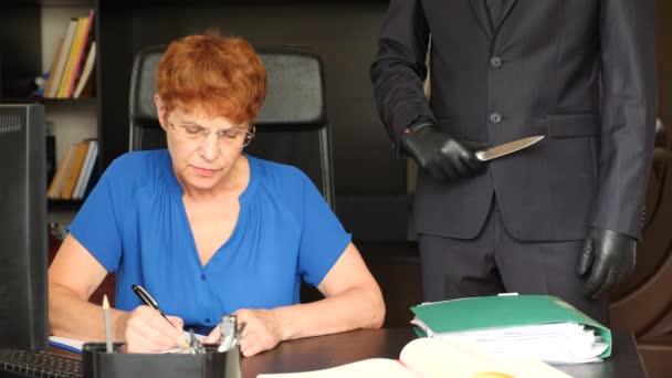 Starší žena podpis bude poslední a zákona sedět na stole. Osoba v obleku za ní chystá pokus o její život. 4k, pomalý pohyb