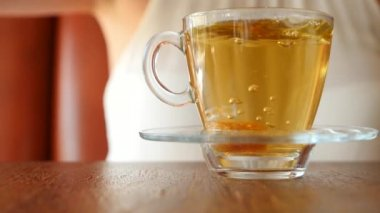 The girl puts a piece of brown sugar in a transparent mug with green tea. Air bubbles rise up. slow motion.
