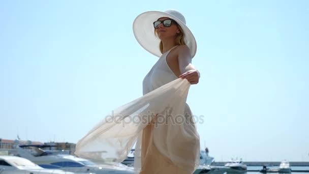 Frau mit Hut und Sonnenbrille im Hintergrund macht Selfie mit Yachten. Mädchen im Rock - die Sonne dreht sich und jubelt. 4k Zeitlupe.