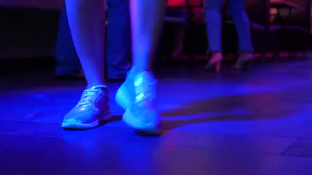 Dámské nohy v stříbrné boty se tančí na tanečním parketu v disco baru. Světlo z safitov. 4k