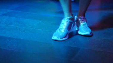 Womens legs in silvery shoes are dancing on the dance floor in the disco bar. Light from safitov. 4k