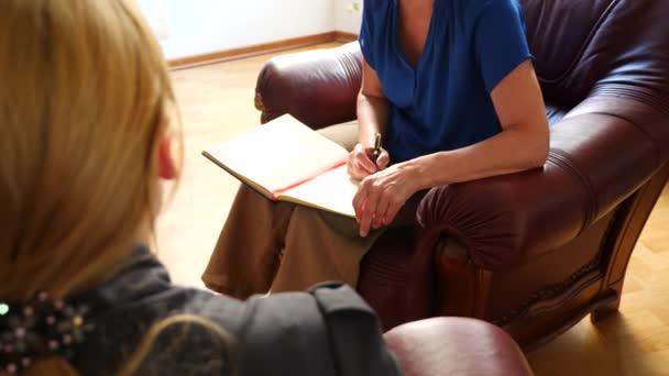 Ženské psycholog dělat poznámky během relace psychologické terapie. smutná žena. 4 k. Zpomalený pohyb