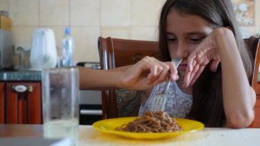 The little girl eats buckwheat noodles with a fork reluctantly. The child refuses to eat. 4 . Slow-motion shooting.